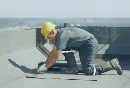 Worker repairing a flat roof in Portland, Oregon.
